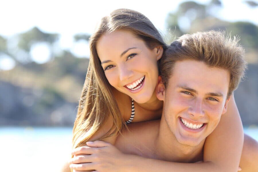teeth whitening Couple with perfect smile posing on the beach